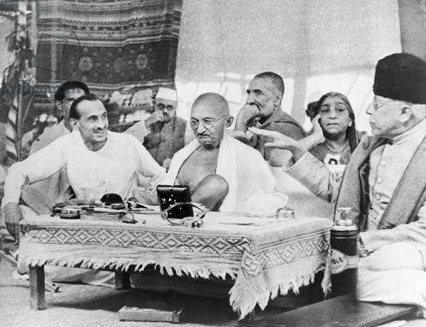 MOHANDAS GANDHI (1869-1948) Hindu nationalist and spiritual leader. Alongside Abul Kalam Azad and J.B. Kripalani in conference with leaders of the All-India Congress Party. Photograph, 1942.