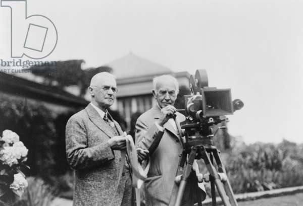 EASTMAN AND EDISON, 1928 American inventors George Eastman and Thomas Edison operating a motion picture camera at Eastman's house in Rochester, New York, during a demonstration on his new Kodacolor film. Photograph, July 1928.