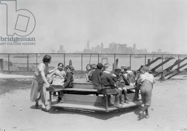 IMMIGRANTS: ELLIS ISLAND Immigrant children at play outside the main hall, with the New York skyline in the background. Photograph by Lewis W. Hine, c.1920.