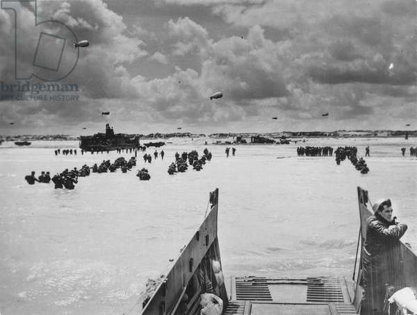 WORLD WAR II: D-DAY, 1944 American troops wade ashore at Utah Beach during the invasion of Normandy, France, 6 June 1944.