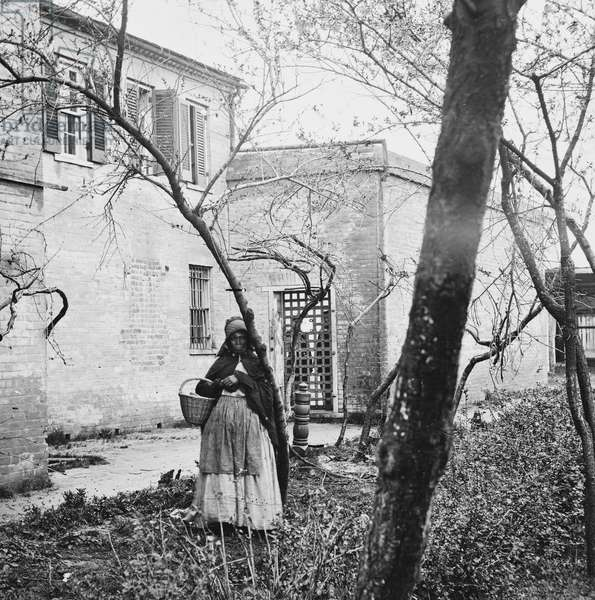 VIRGINIA: SLAVE PEN, c.1861 An African American woman standing in front of a slave pen in Alexandria, Virginia. Stereograph, c.1861-1869.