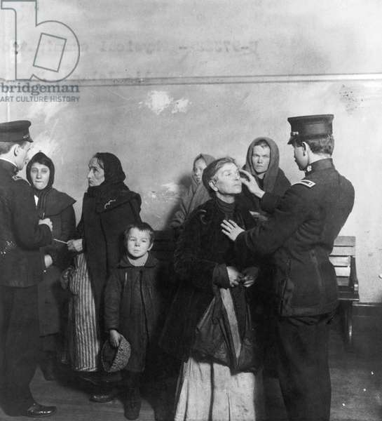 ELLIS ISLAND: INSPECTION Federal inspectors examining the eyes of immigrants at the immigration station in New York Harbor, c.1911.