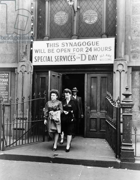 D-DAY SERVICES, 1944 Women and men exiting a synagogue on West 33rd Street after D-Day services in New York City. Photograph, June 1944.