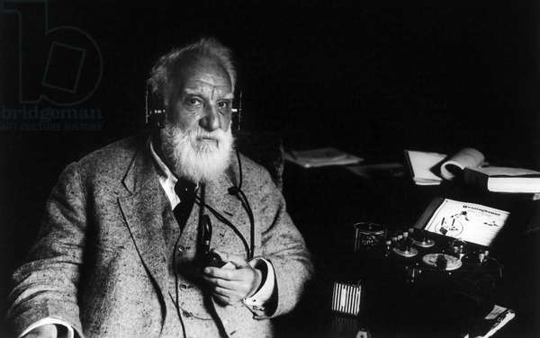 ALEXANDER GRAHAM BELL (1847-1922) American (Scottish-born) teacher and inventor. Photographed with a radiophone, holding pipe, and wearing headphones on 5 May 1922.