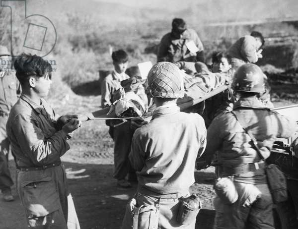 KOREAN WAR: WOUNDED, 1952. A South Korean infantryman, wounded in the fighting for Triangle Hill, is lifted from a vehicle at the aid station, 2 November 1952.