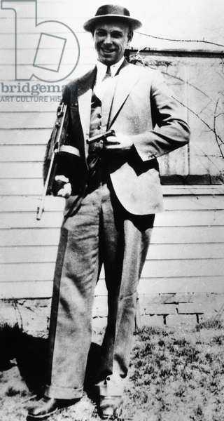JOHN DILLINGER (1903-1934) American bank robber. Photographed in 1934 at his father's home in Mooresville, Indiana, holding a submachine gun and the wooden gun that he claimed he used to escaspe from jail in Crown Point, Indiana.