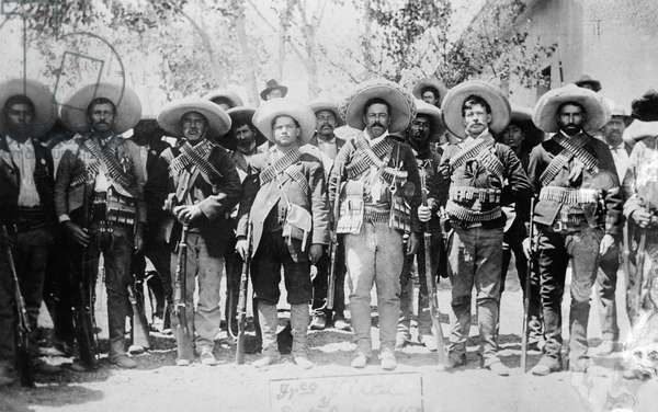 FRANCISCO 'PANCHO' VILLA (1878-1923). Mexican revolutionary leader. Photographed wearing bandoliers with his military staff during the Mexican Revolution, c.1913.
