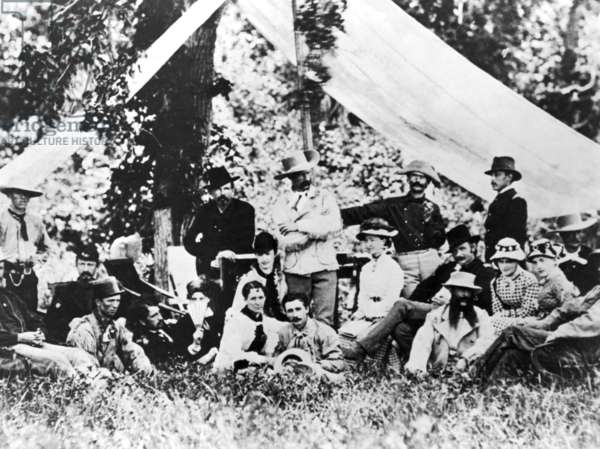 GEORGE CUSTER (1839-1876) American army officer. Custer (center in buckskins) with officers of the 7th Cavalry and their wives at Little Heart River, Dakota Territory in 1875. Elizabeth Custer sits at the right of her husband.