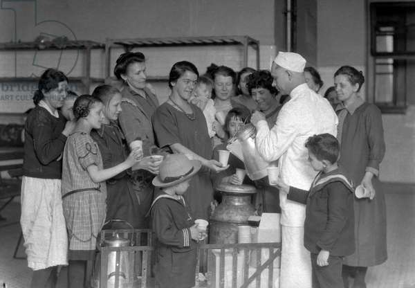 ELLIS ISLAND, c.1917 Immigrants being served milk in the waiting room. Photograph, c.1917.