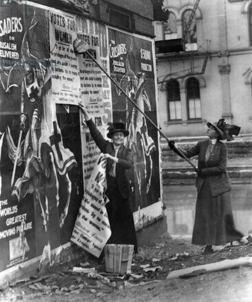 CINCINNATI: SUFFRAGETTES Suffragettes Louise Hall and Susan Fitzgerald pasting signs for 'Votes For Women' on a street in Cincinnati, Ohio, 1912.