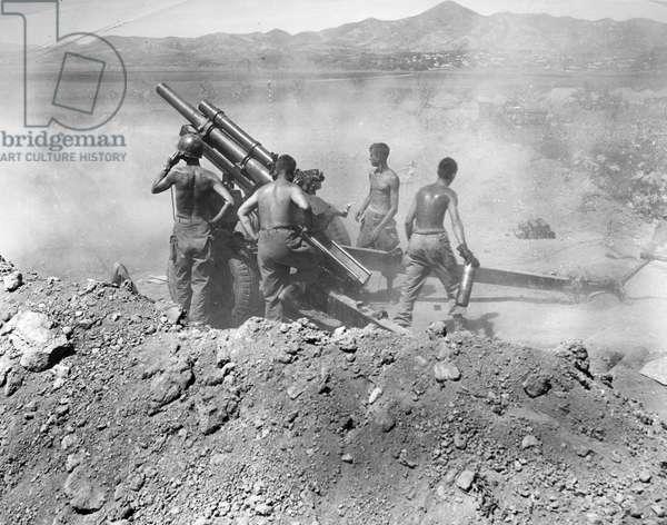 KOREAN WAR: ARTILLERY U.S. artillerymen firing a 105mm howitzer on North Korean positions near Uirson, South Korea, August 1950.