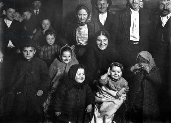 ELLIS ISLAND: IMMIGRANTS Group of very happy immigrants, newly arrived at Ellis Island, New York City. Photograph, late 19th or early 20th century.