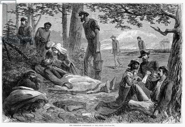 CIVIL WAR: WOUNDED Volunteers of the Christian Commission give first aid to wounded Union soldiers at a battlefield during the American Civil War. Wood engraving from a Northern American newspaper of 1864.