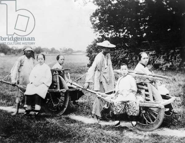 CHINA: WHEELBARROWS, c.1915 Wealthy Chinese women travellng in wheelbarrows pushed by men, China. Photograph, c.1915.