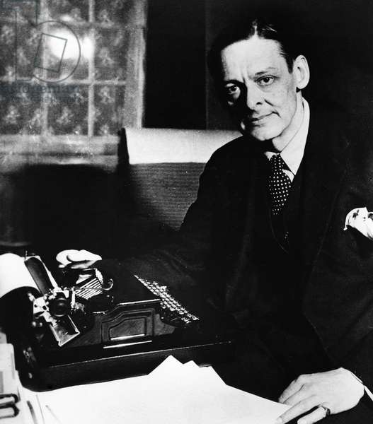 T.S. ELIOT (1888-1965) Thomas Stearns Eliot. American (naturalized British) poet and critic. Photographed at his typewriter, c.1945.