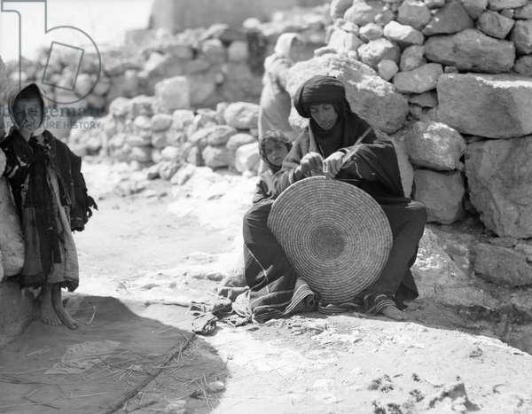 JORDAN: BEDOUIN WEAVING A Bedouin woman weaving a straw mat, accompanied by two young boys, at Umm Qais, Jordan. Photograph, 1920s or 1930s.