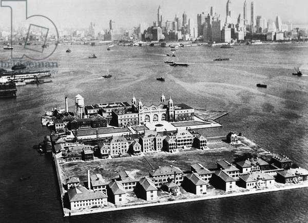 ELLIS ISLAND, 1933 Ellis Island, the immigration station in New York Harbor and the Manhattan skyline, 1933.