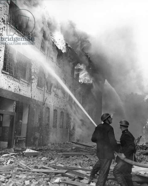 WWII: LONDON BLITZ, 1944 Firemen fight flames at Regency Place and Rutherford Street, London, following a German plane attack in 1944.