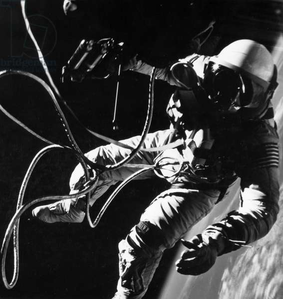 SPACE: GEMINI 4, 1965 Astronaut Edward H. White performing his spectacular space feat during the 3rd orbit of the Gemini-Titan 4 flight. White floats into space, secured to the Gemini 4 spacecraft by a 25 foot umbilical line and a 23 foot tether line, 3 June 1965.