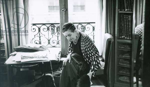 JEANNE LANVIN (1867-1946) French fashion designer. Choosing between a red fox and a blue fox to complement a rust fabric while working on the fall collection in her office at the House of Lanvin, 1937.
