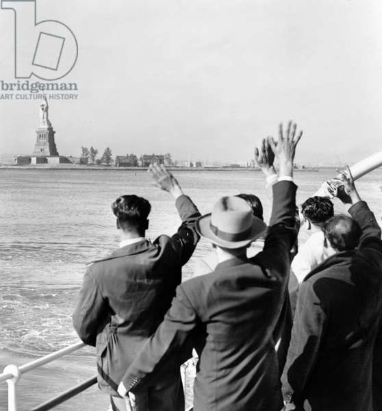 STATUE OF LIBERTY Part of a group of illegal immigrants waving goodbye to the Statue of Liberty from the Coast Guard cutter that took them from Ellis Island to the Home Lines ship 'Argentina' in Hoboken for deportation. Photographed by Al Ravenna, c.1952.