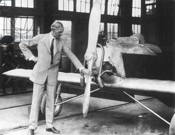 """HENRY FORD (1863-1947). American automobile manufacturer. Photographed inspecting the Ford """"Flying Flivver"""" (18 ft. wing to wing, 300 lbs.)."""