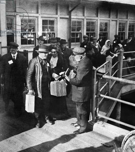 ELLIS ISLAND: IMMIGRANTS Man distributing bibles to immigrants arriving at Ellis Island, New York City. Stereograph, c.1911.