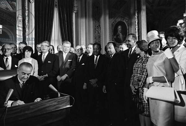 LYNDON BAINES JOHNSON (1908-1973). 36th President of the United States. Signing the Voting Rights Act, as Martin Luther King Jr. and other civil rights leaders look on. Photograph by Yoichi Okamoto, 6 August 1965.