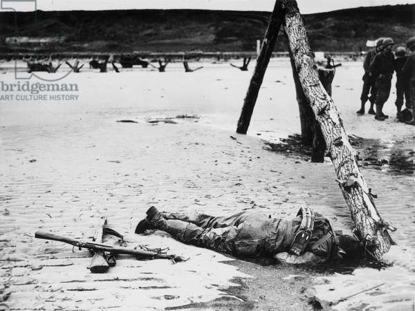 WORLD WAR II: D-DAY, 1944 An American soldier lies dead alongside an anti-landing craft obstruction on Omaha Beach during the invasion of Normandy, 6 June 1944.