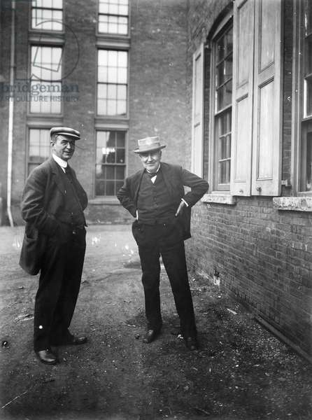 THOMAS EDISON (1847-1931) American inventor. Edison (right) and an unidentified man outside of Edison's West Orange, New Jersey laboratory.