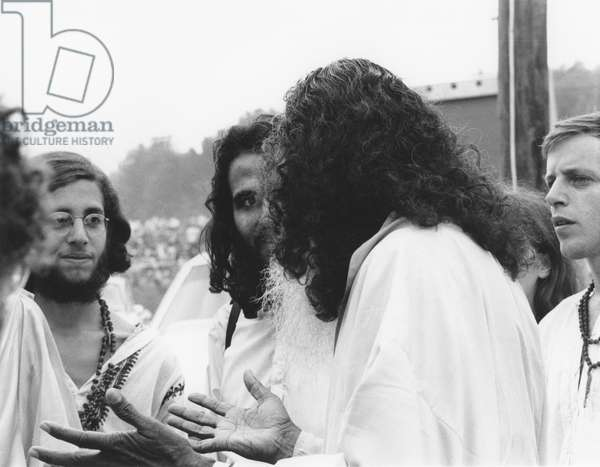 HIPPIE MOVEMENT, 1969 A guru speaks with several followers at the Woodstock rock concert in upstate New York.