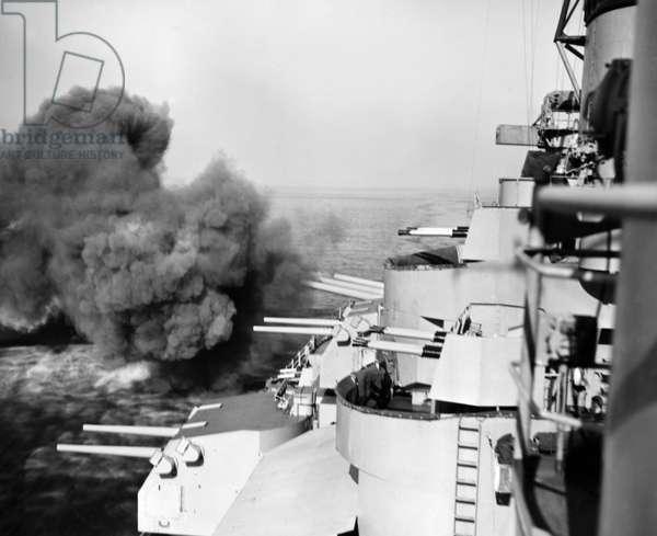 KOREAN WAR: USS IOWA, 1952 Sixteen-inch turret guns of the USS Iowa fire at a railroad tunnel on the east coast of North Korea, May 1952.