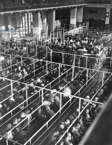 ELLIS ISLAND, 1906 Clearance lines in the registry room of the immigration station in New York Harbor, Christmas 1906.
