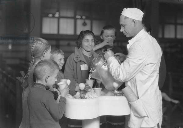 ELLIS ISLAND, c.1917 Immigrants being served milk in the waiting room of Ellis Island, New York. Photograph by Lewis W. Hine, c.1917.