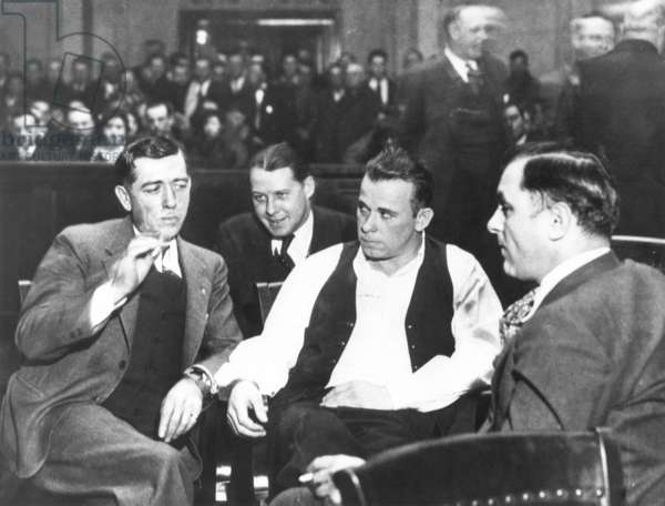JOHN DILLINGER (1903-1934) American bank robber. Dillinger (wearing open vest) surrounded by guards at his arraignment in court in Crown Point, Indiana, on 9 February, 1934, on the charge of killing a policeman in East Chicago, Indiana.