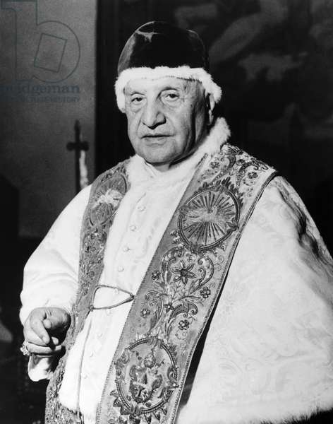 JOHN XXIII (1881-1963) Pope, 1958-1963. Photographed in his private library in the Palazzo Apostolico in Vatican City, wearing his red velvet 'camauro,' 15 April 1963.