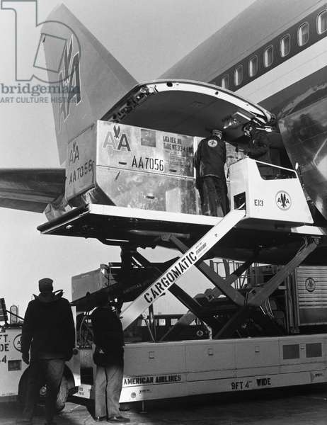 AMERICAN AIRLINES CARGO Men loading cargo onto a Boeing 747 airplane operated by American Airlines. Photograph, late 20th century.