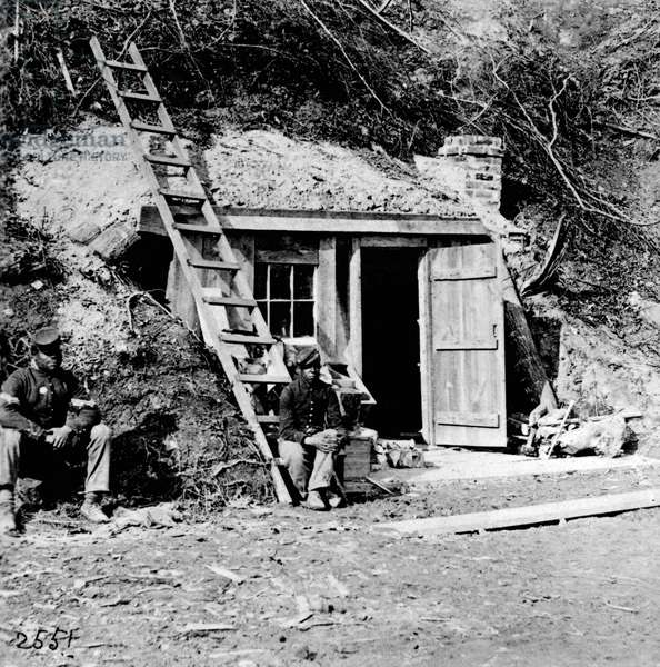 CIVIL WAR: DUTCH GAP CANAL Two African American soldiers outside a small building near the Dutch Gap Canal of the James River in Virginia, during the Civil War. Photograph, 1864.