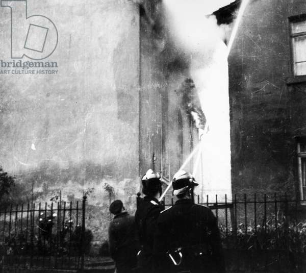 KRISTALLNACHT, 1938 Firefighters in Ober-Ramstadt, Germany, working to prevent fires from spreading from the synagogue to nearby homes, while permitting the synagogue to continue burning in the aftermath of the Kristallnacht pogrom, 9-10 November 1938.