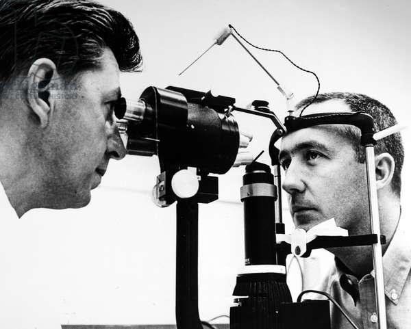 JAMES McDIVITT (1929-) Astronaut James McDivitt, command pilot of the Gemini IV flight, receiving an eye exam from Dr. James Culver, Air Force lieutenant colonel, during the pre-flight physical examination, 1 June 1965.