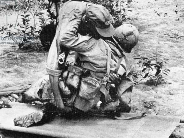 VIETNAM WAR: WOUNDED, 1966 A medic helps a wounded American soldier onto a stretcher at Dak To, South Vietnam, November 1966.
