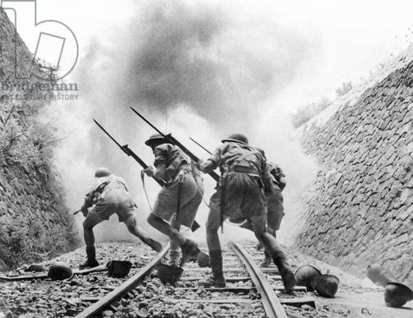 WORLD WAR II: SICILY. With bayonets fixed to their rifles, soldiers of the British Eighth Army advance through a disused rail cutting to take a railway strongpoint in Sicily, August 1943.