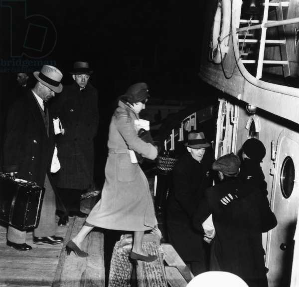 DEPORTATION, 1940 Deportees boarding a boat en route to Ellis Island, to await deportation to their home countries. Photograph, c.1940.