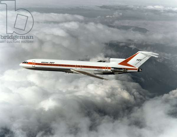 BOEING 727 AIRPLANE A Boeing 727 passenger plane in flight. Photograph, mid or late 20th century.