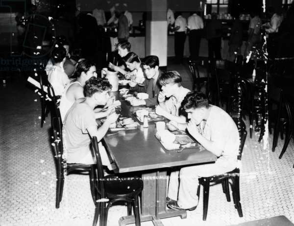ELLIS ISLAND, 1947 Men awaiting deportation from Ellis Island having a meal in the dining room. Photograph by Hans Reinhart, 1947.