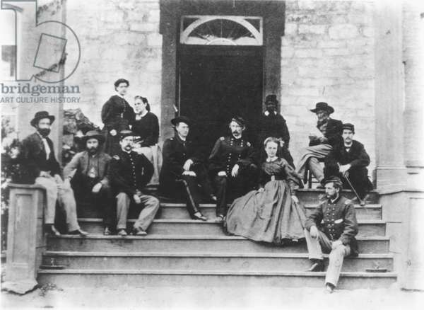 GEORGE ARMSTRONG CUSTER (1839-1876). American army officer. Custer at center right between his wife, Elizabeth, and brother, Tom; his father reads at upper right: photographed at Winter quarters in 1865.