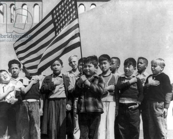 A group of children, including many Japanese Americans, at the Raphael Weill School in San Francisco, saluting the American flag, April 1942 (b/w photo)