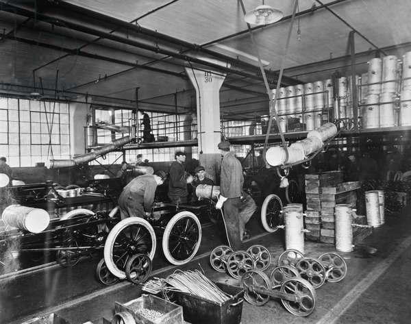 FORD ASSEMBLY LINE, c.1913 Workers installing gas tanks at the assembly line at the Ford automobile plant in Highland Park, Michigan, c.1913.