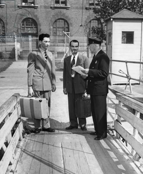 ELLIS ISLAND, c.1940 Italian men arriving at Ellis Island. Photograph, c.1940.