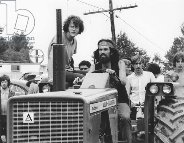 WOODSTOCK, 1969 Hippies ride a tractor behind the scenes at the famous Woodstock music festival.